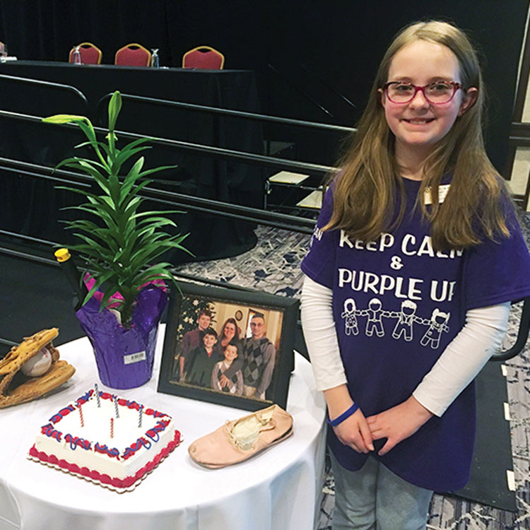 An ALA Junior member stands next to a Military Child's Table Setting. You can honor our military children on April 15 with the designated holiday: Purple Up! Day.
